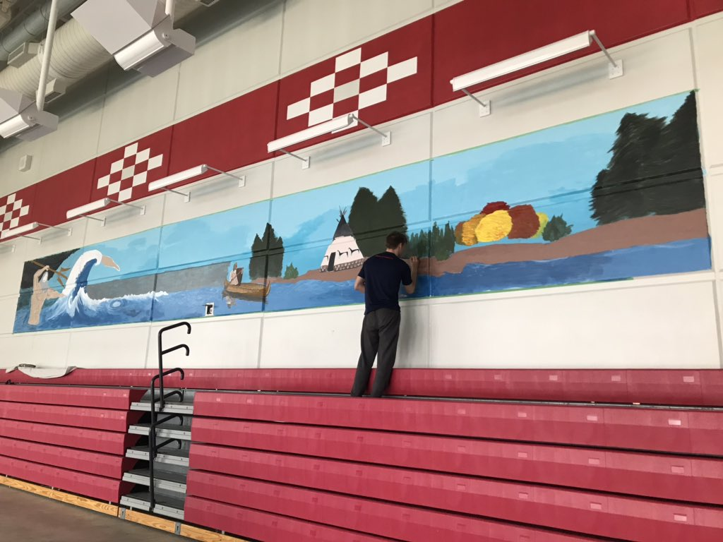 Josiah Connelly adds details to his mural in the pool.